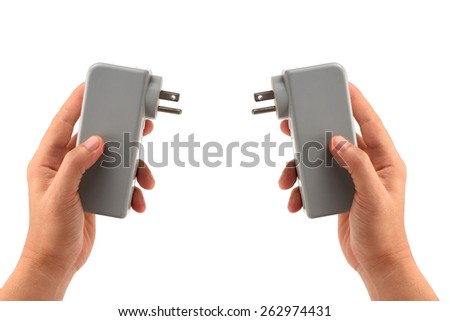 two-sided hand holding adapter Plugs isolated on white - stock photo