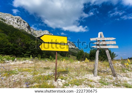 Two signposts on crossroad at mountain and forest - stock photo