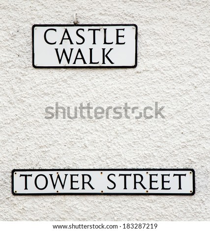 Two signs against a white wall near an ancient castle - stock photo