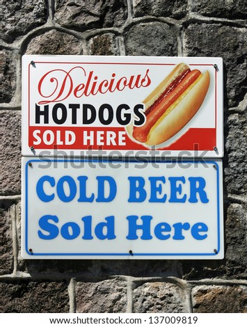 Two signs that advertise hot dogs and cold beer - stock photo