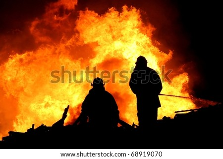 Two silhouetted firemen fighting a large fire - stock photo