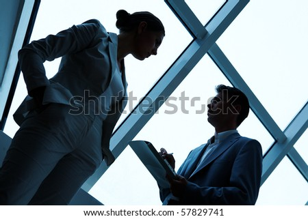 Two silhouettes of businesspeople interacting with each other in the office