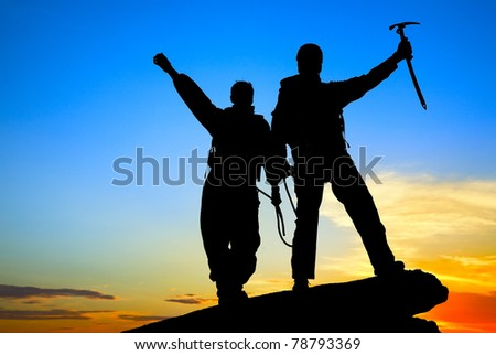 Two silhouettes of climbers on the mountain top - stock photo