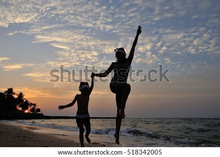 Two silhouettes on the beach with a background of a golden sunset: mom and his five year old son are jumping high. On the heads of both is Santaâ??s red cap. Wet sand and sea water reflects the sunshine
