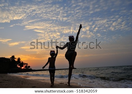 Two silhouettes on the beach with a background of a orange sunset: mom and his five year old son are jumping high. On the heads of both is Santaâ??s cap. Blue and orange sky looks fabulous