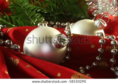 two silver Christmas balls and tinsel chain lie on red fabric - stock photo