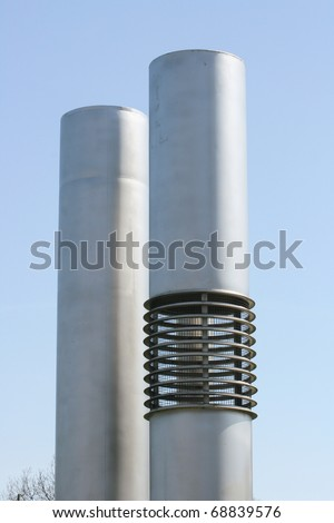 two silver-colored exhaust pipes with blue sky in the background