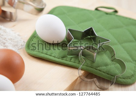 two silver cookie mold with white egg on wooden table and green napkin