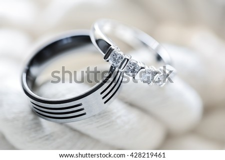 Two silver platinum and titanium diamond wedding rings on white rope background - stock photo