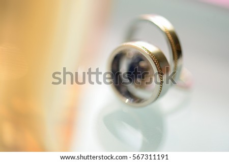 two silver wedding rings on glass table