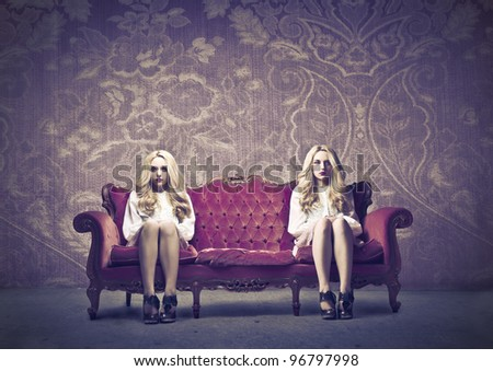 Two similar women sitting on a sofa - stock photo