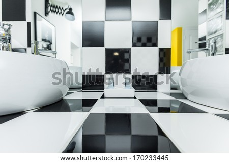 Two sinks in modern bathroom with checkered black and white tiles on walls. - stock photo