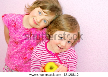 Two sister standing next to each other, face to face. They both dressed in pink clothes and they happily smile. In the hands of the child's great apple. Siblings.