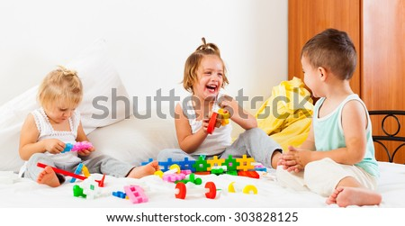 Two sisters and  brother having fun on white bed. - stock photo