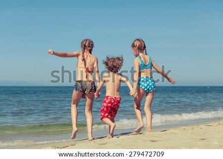 two sisters and brother playing on the beach at the day time - stock photo