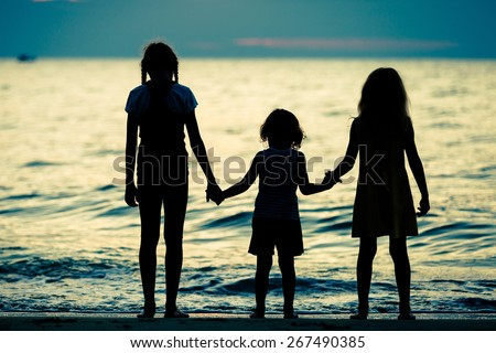 two sisters and brother standing on the beach at the sunset time - stock photo