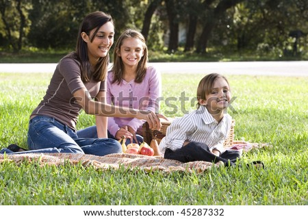 Two sisters and little brother playing on picnic blanket in park - stock photo