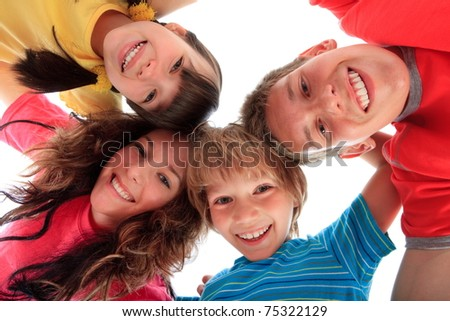 Two sisters and two brothers with their heads together forming a circle looking at the viewer from above, isolated on a white background. - stock photo