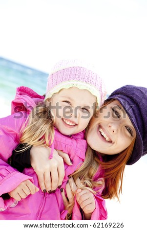 Two sisters 4 and 21 years old at the beach in sunny autumn day. - stock photo