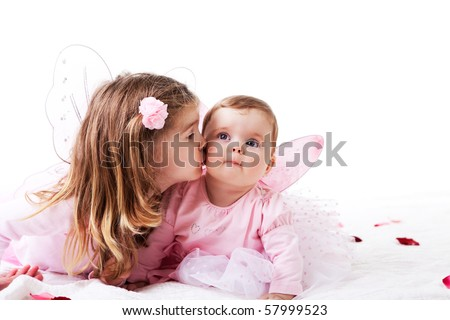 Two sisters are dressed up as fairies.  Horizontal shot. - stock photo