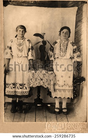 Two  sisters are looking at camera in ukrainian dresses,1914 year.