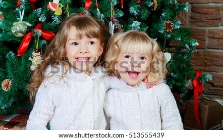two sisters at home with the Christmas tree and presents