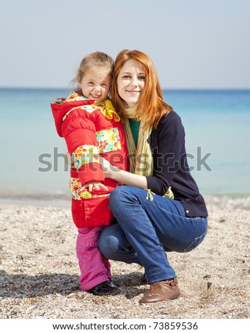 Two sisters at the beach in spring day. - stock photo