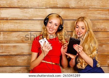 Two sisters, blonde, listening to music on headphones. Girl looking at the camera, holding a cell phone, and the other on screen tablet pc. Sisters sitting in the bedroom. - stock photo