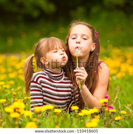 Two sisters blowing dandelion seeds away. - stock photo