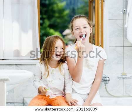 Two sisters cleaning the teeth together, morning, bathroom - stock photo