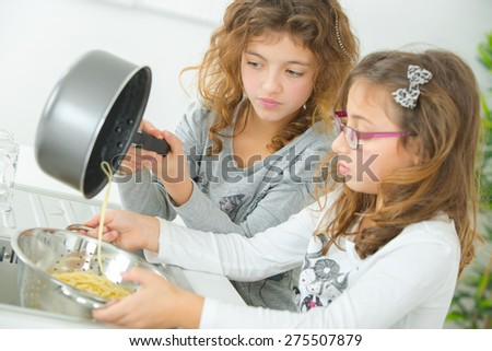 Two sisters cooking together - stock photo