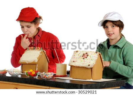 Two sisters decorating gingerbread houses together.  Isolated on white. - stock photo