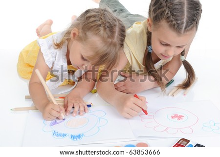 Two sisters draw on the album in a bright room. Isolated on white background - stock photo