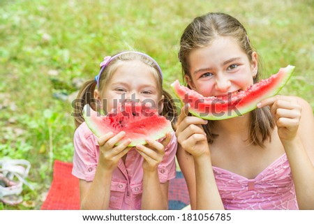 Two sisters eating fresh watermelon on green grass background