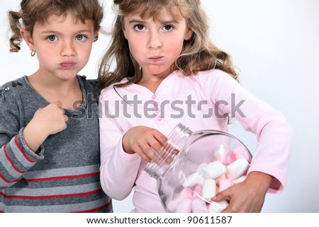Two sisters eating marshmallows. - stock photo