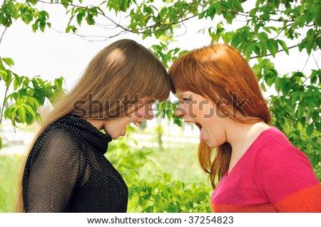 two sisters engaged in a heated argument - stock photo