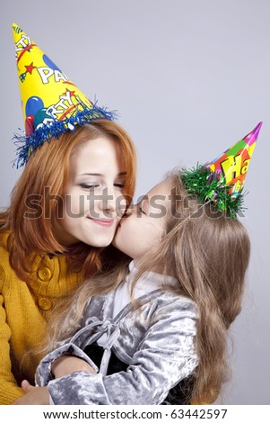 Two sisters four and eighteen years old at birthday. Studio shot. - stock photo