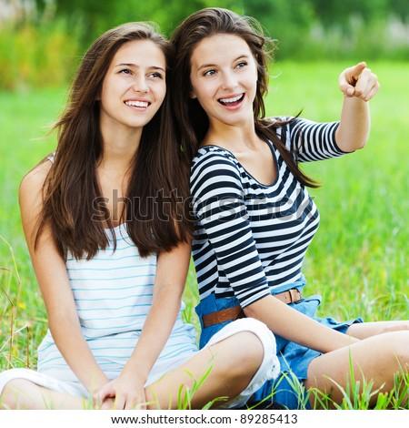 two sisters girlfriends long dark hair sitting cross-legged grass park talking - stock photo