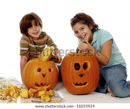 Two sisters happily displaying the pumpkins they've just carved for Halloween. - stock photo