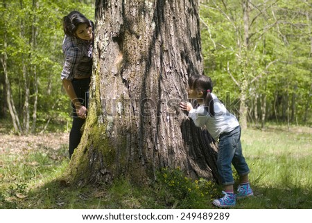Two sisters hiding behind tree