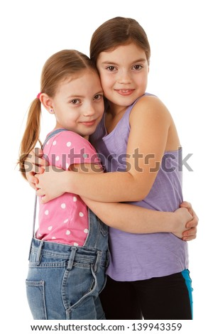 Two sisters hugging and smiling. Isolated studio shot.