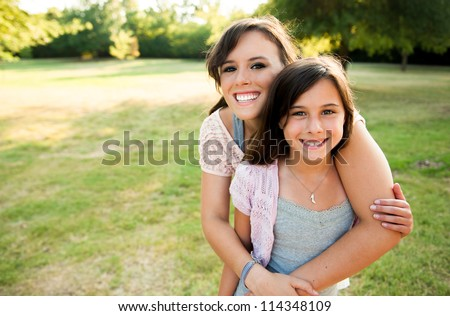 Two sisters hugging outside smiling - stock photo