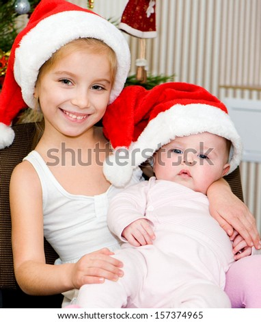 two sisters in front of christmas tree