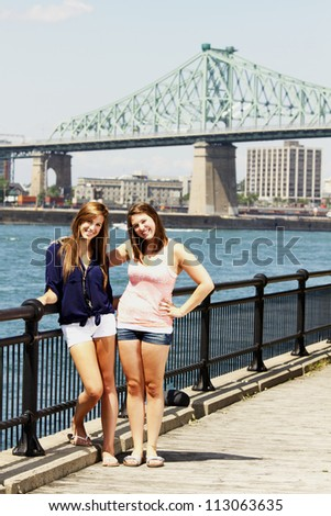 Two sisters interacting with bridge and cityscape behind - stock photo