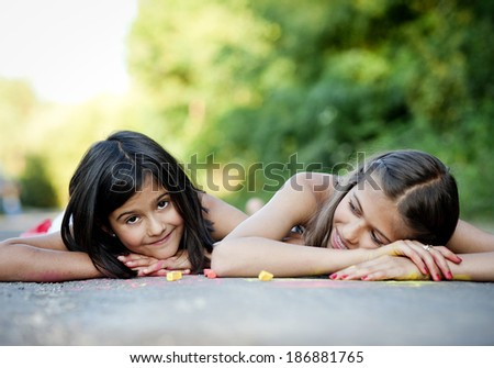 Two sisters laughing and playing with chalks on pavement in green sunny park - stock photo