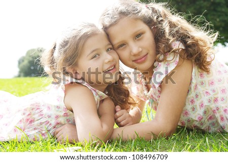 Two sisters laying down on green grass in the park, facing each other and smiling. - stock photo