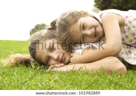 Two sisters laying down on top of each other and smiling in the park. - stock photo