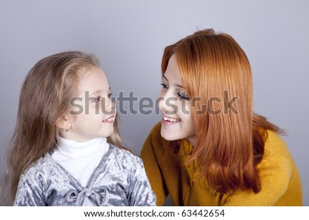 Two sisters looking at at each other. Studio shot. - stock photo