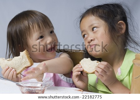 Two sisters making a mess with peanut butter and jelly - stock photo