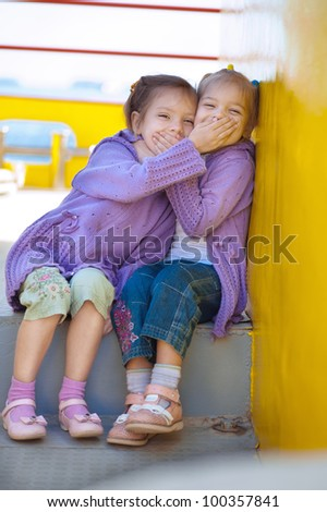 Two sisters on ship close to each other mouths. - stock photo